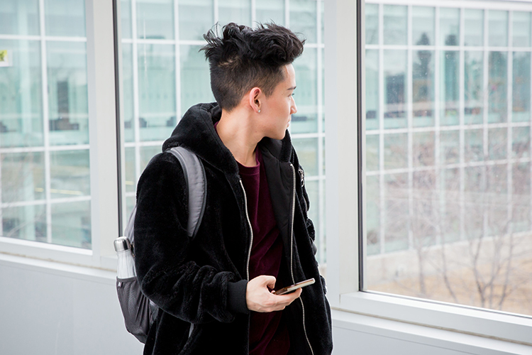 NAIT student walking in the hallway holding a cell phone.