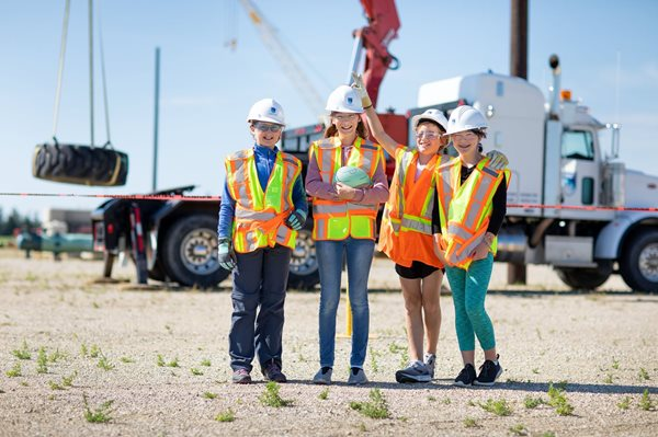 Four girls standing together at a construction site in summer wearing hard hats and PPE