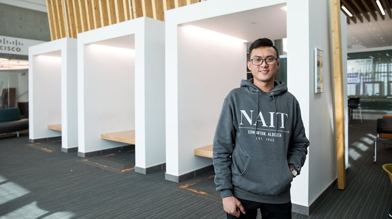 Student in grey NAIT hoodie standing in front of modern-looking collaboration space.